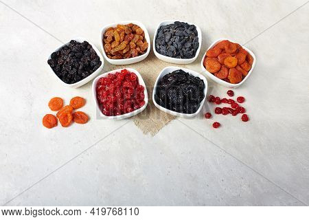 Different Dried Fruits: Prunes, Raisins, Dates, Dried Apricots And Cherries In A Bowls