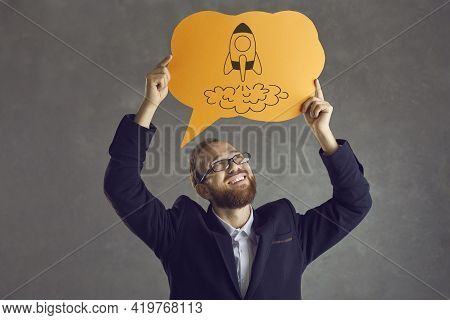 Happy Businessman In Suit And Glasses Holding Speech Balloon With Picture Of Space Rocket