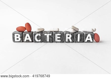Bacteria The Word On Stone Cubes. Cubes Stand On A White Surface, Many White And Red Pills. Medicine