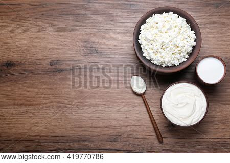 Clay Dishware With Fresh Dairy Products On Wooden Table, Flat Lay. Space For Text