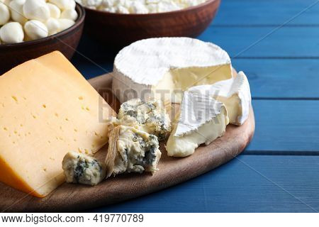 Fresh Dairy Products Near Clay Dishware On Blue Wooden Table