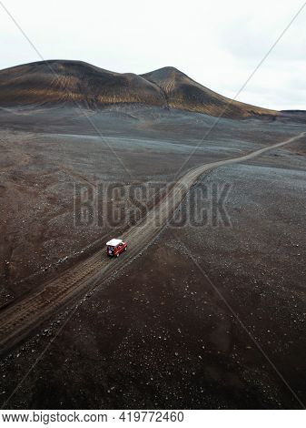 Drone view of a Suzuki Jimny driving on a dirt road