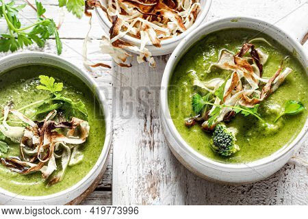 Homemade broccoli soup with horseradish and parsley chips
