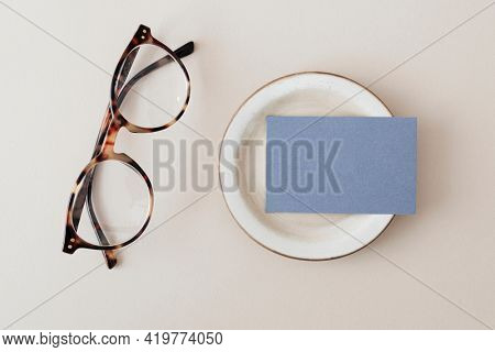 Blue business card on a plate with glasses mockup
