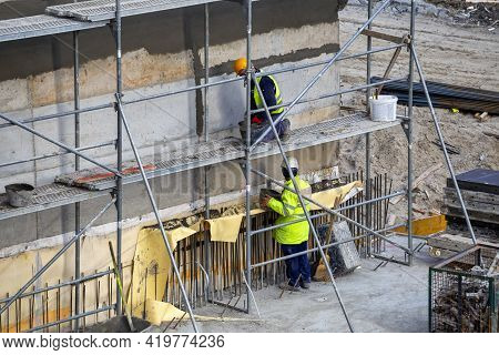 Scaffolding Builder With Trowel Plastering Cement Wall