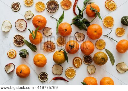 Dried oranges and clementines on a marble countertop