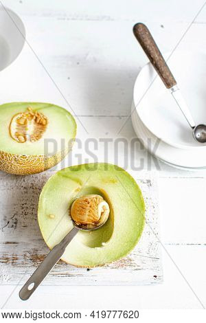 Scooping out the seeds and flesh of a melon