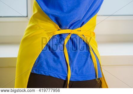 Close Up Of Unrecognizable Person Wearing Tied Up Yellow Apron. Household Duties Concept