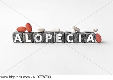 Alopecia The Word On Stone Cubes. Cubes Stand On A White Surface, Many White And Red Pills. Medicine