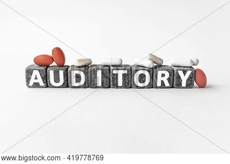 Auditory The Word On Stone Cubes. Cubes Stand On A White Surface, Many White And Red Pills. Medicine