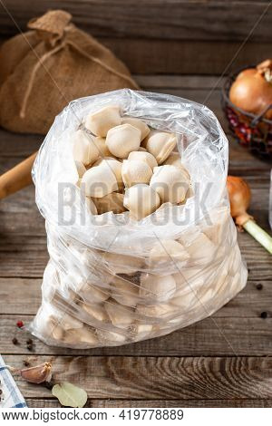 Frozen Meat Dumplings In A Plastic Bag On Wooden Background. Semi-finished Products