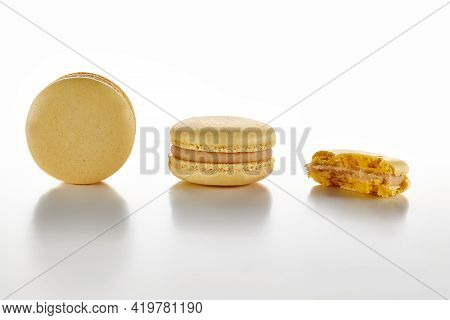 Two Whole And One Bitten Macarons On White Surface