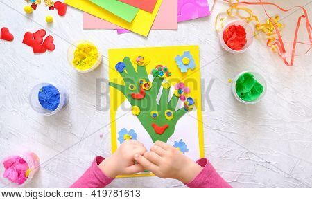Little Girl Making Homemade Greeting Card From Envelope, Paper And Colodful Clay, Plasticine As Gift