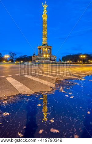 The Famous Victory Column In The Tiergarten In Berlin, Germany, At Dusk, With A Reflection In A Pudd