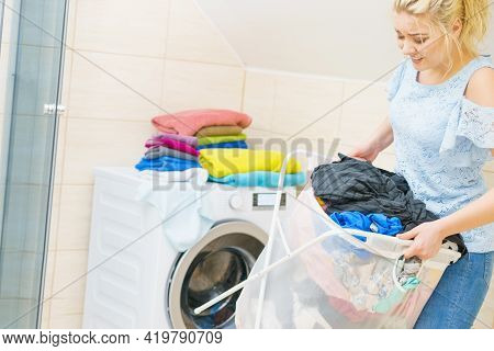 Woman Having Troubles With Holding Big Laundry Basket Full Of Colorful Dirty Clothes. Bathroom Utens