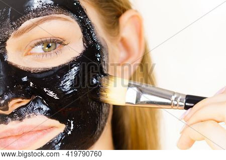 Woman Applying Black Mud Mask To Face
