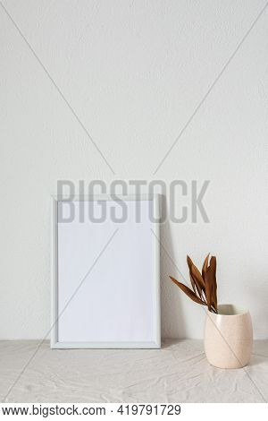 Home Decor Mocap, Empty Picture Frame Near White Painted Concrete Wall, Branches With Dry Leaves