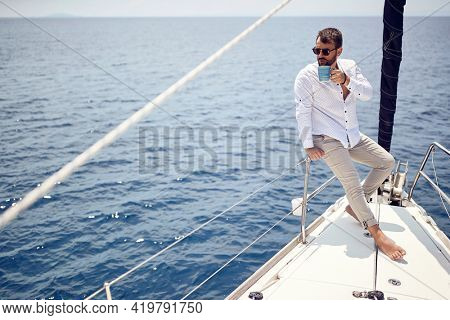 A young handsome barefoot male model is enjoying the view at a photo shooting on a yacht on a beautiful sunny day on the seaside. Summer, sea, vacation