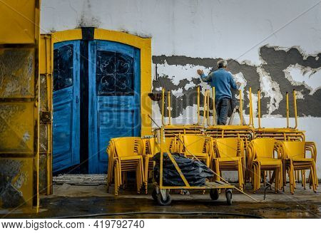 Lisbon, Portugal - January 21, 2017: Old Man Painting A Wall. Traditional Painter Job, Colorful Blue