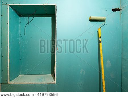 Green Plasterboard Or Drywall And Yellow Roller For Painting Gypsum Walls In Apartment Is Under Cons