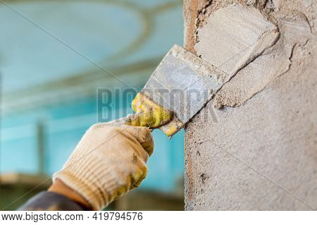 Worker Is Cementing By The Putty Knife The Wall In Room That Is Under Construction, Remodeling, Reno