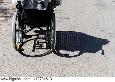 Shadow Of The Wheelchair And The Tires. Shadow Of A Woman Sitting On A Wheelchair. Invisible Women S