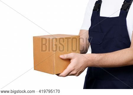 Side View Of Body Of Man In Dark Blue Overalls And And A White T-shirt Giving Cardboard Box, Isolate