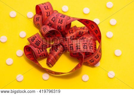 A Red Measuring Tape For Measuring The Circumference Of The Body, Abdomen, Hips Is On A Yellow Backg