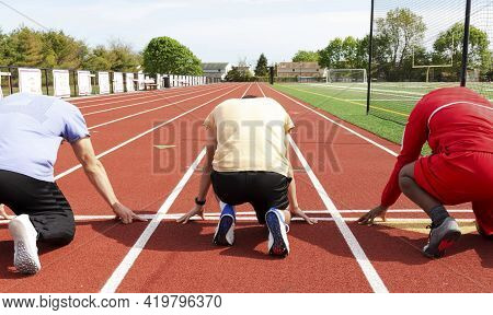 Rear View Of Three High School Male Sprinter Runners Ready On Their Mark At The Start Line At Track