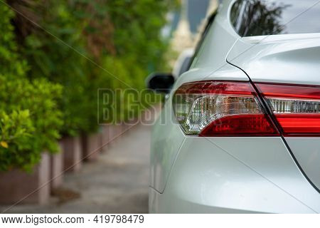 A White Car Parked On The Roadside With A Natural Background.