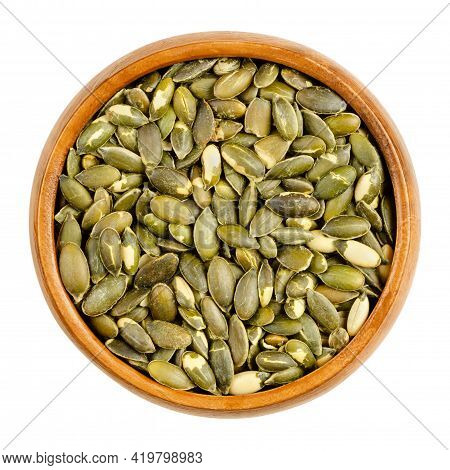 Hulled, Roasted, Salted Pumpkin Seeds, In A Wooden Bowl. Edible, Flat, Green Squash Seeds, Also Know