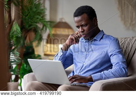 Young Serious African Man Typing On Laptop At Home