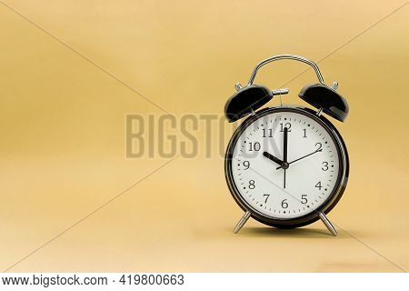 Black Alarm Clock And Space For Text. Retro Alarm Clock On Sand Background