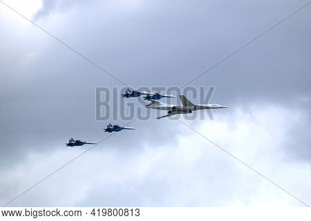 MOSCOW, RUSSIA - May 7, 2021: Russian military Supersonic bomber-missile carrier TU-160 Whire Swan and four SU-35S fighters following on the sides flying in cloudy sky on parade rehearsal