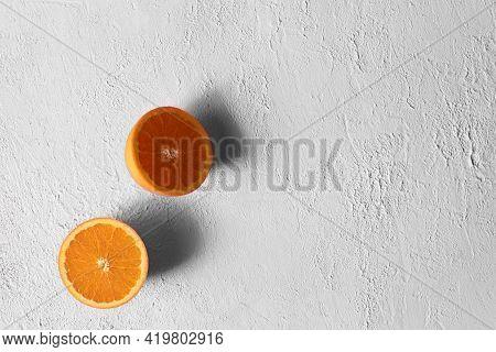 Ripe Orange Cut In Half On A Gray Concrete Surface. Minimalism. Copy Space