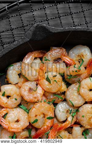Prawns Fried With Garlic In A Cast Iron Skillet On A Black Wooden Table. Top View. Copy Space