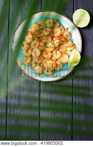 Prawns Fried With Garlic On A Blue Porcelain Plate With A Slice Of Lime On A Black Wooden Table. Ver