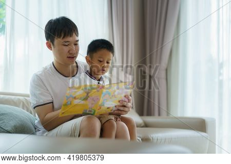 Asian Father Holds A Book To Teach His Children To Read On The Sofa In The Living Room, Fathers Inte