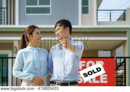 Portrait Of Asian Young Couple Standing And Hugging Together And Holding House Key Looking Happy In