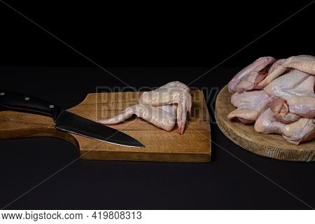 Raw Chicken Wings On A Black Background. Fresh Chicken Meat. Cooking Chicken Wings