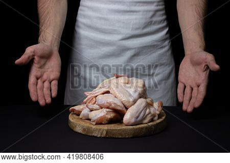 Raw Chicken Wings On A Black Background. The Chef Prepares Chicken Wings On A Dark Background. Fresh