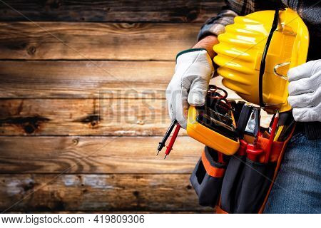 Electrician Worker On Vintage Wooden Background; Holds The Multimeter Tester, Helmet And Protective