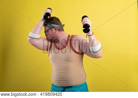 Funny Fat Man Goes In For Sports. Does A Dumbbell Biceps Exercise