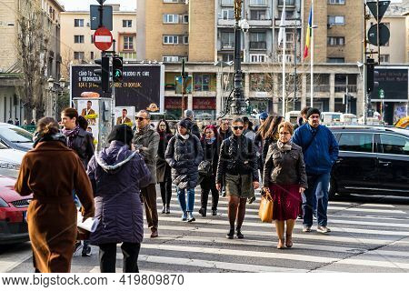 People At Zebra Crossing, Pedestrians Crossing The Street In Downtown Area Of Bucharest, Romania, 20