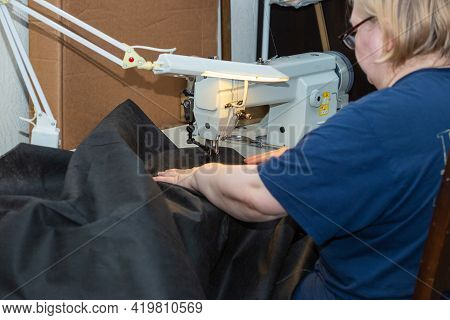 A Woman Seamstress Sews A Black Cloth On An Industrial Sewing Machine, Sewing Process