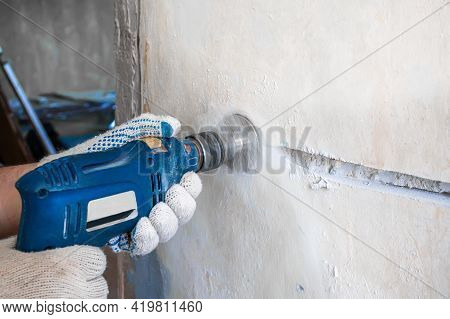 Aworker Drills A Hole For An Electrical Outlet In A Concrete Brick Wall. Repair Of Electrical Wiring