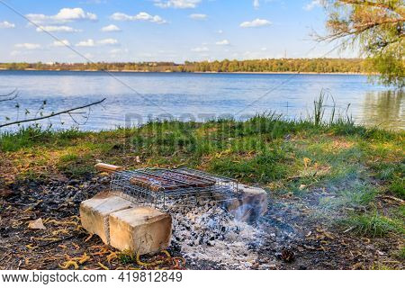 Grilling Sausages In Portable Barbecue Grill On Campfire At Riverbank