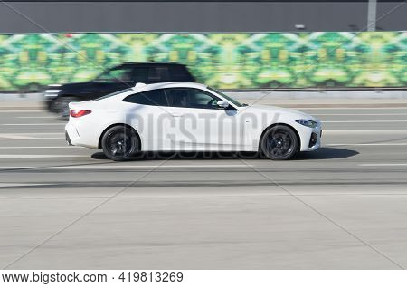 White Bmw M440i Xdrive Coupe On The City Road. Fast Moving Vehicle On The Street. M Sport Coupe Driv