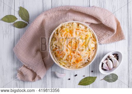 Top View Of A Ceramic Bowl With Fermented Sauerkraut And Spices On A Light Wooden Surface. Healthy F