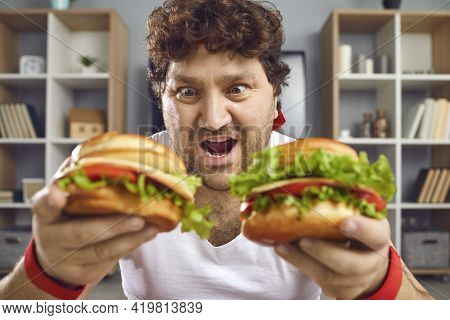 Hungry Chubby Man Looking At Two Delicious Hamburgers With Funny Face Expression